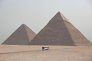 The Giza Plateau with Khafre pyramid on right Khufu pyramid on left in background, tour bus on main road