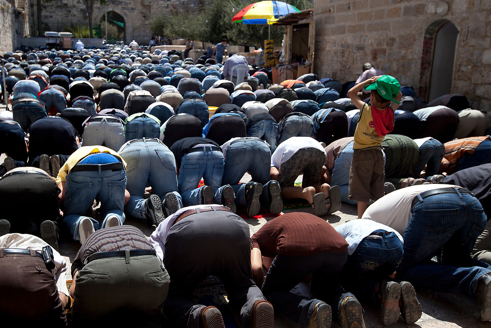 A Muslim boy stands between Muslim worshippers particiapting in the last friday prayers of the Muslim holy month of Ramadan, outside the Al Aqsa Mosque in Jerusalem, September 3, 2010.