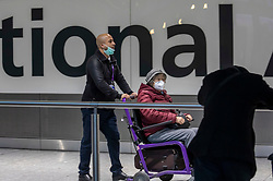 © Licensed to London News Pictures. 29/01/2020. London, UK. Passengers with protective mask at London Heathrow Terminal 5 as the last BA flight from China arrives. The coronavirus virus has infected more than 40000 people across Asia in the past few weeks. Photo credit: Alex Lentati/LNP