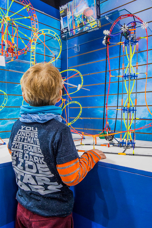 Ashley Napier and his four year old son visit the Knex stand (the boy in  a Star Wars shirt is clearly intrigued and sometimes delighted with the complex constructions) - The annual London Toy Fair, the trade show for the toy and games industry, takes place at Olympia.