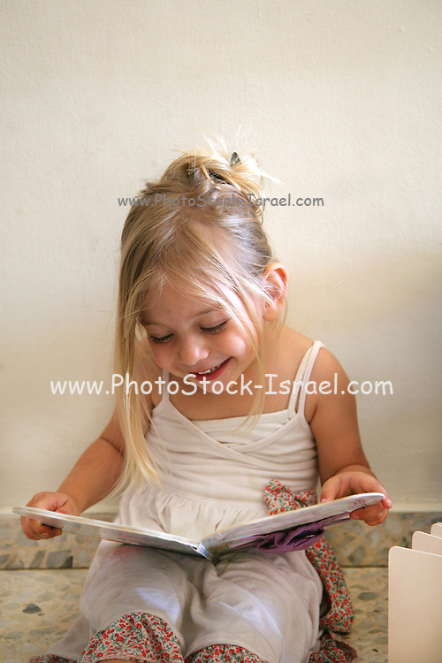 Girl of three reads a book