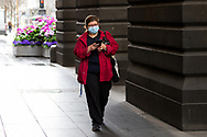 A woman wearing a facemask is seen walking by the Melbourne Town Hall during COVID-19 in Melbourne, Australia. Victoria has recorded 14 COVID related deaths including a 20 year old, marking the youngest to die from Coronavirus in Australia, and an additional 372 new cases overnight. (Photo by Dave Hewison/Speed Media)