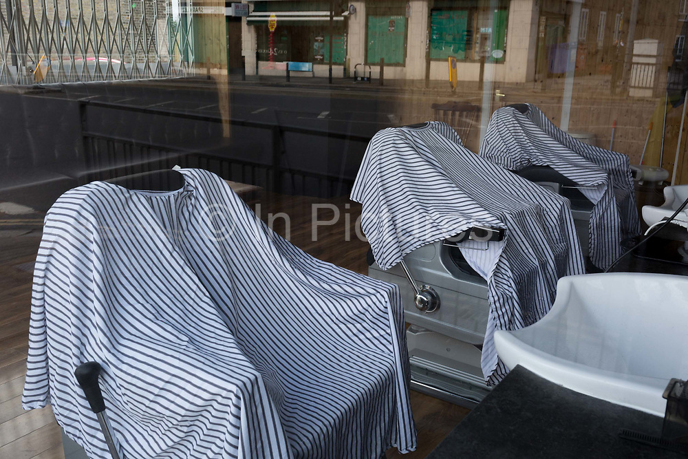 At the beginning of the second week of the UKs Coronavirus lockdown and in accordance with government guidelines for social distancing and the forced closure of all shops and local businesses, hairdressing gowns hang on the backs of chairs in a closed mens barbers business in East Dulwich, on 30th March 2020, in London.