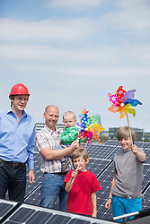 Two men father kids toy windmill solar park