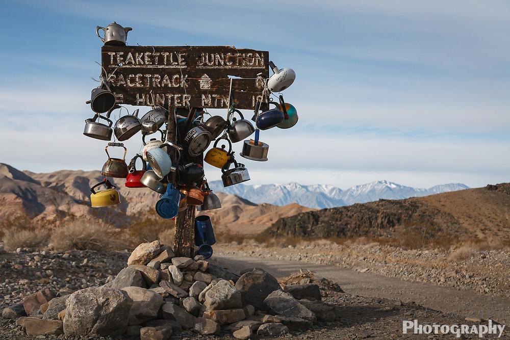 Desert scene, teakettles hang on a sign post at Teapot Junction in Death Valley National Park