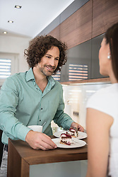 Man serving slice of cake to his wife, Munich, Bavaria, Germany