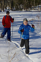 Jessica  and Russell Laman cross country skiing in the New England woods.