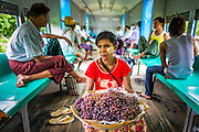 15 JUNE 2013 - YANGON, MYANMAR: A grape vendor on the Yangon Circular Train. The Yangon Circular Railway is the local commuter rail network that serves the Yangon metropolitan area. Operated by Myanmar Railways, the 45.9-kilometre (28.5 mi) 39-station loop system connects satellite towns and suburban areas to the city. The railway has about 200 coaches, runs 20 times and sells 100,000 to 150,000 tickets daily. The loop, which takes about three hours to complete, is a popular for tourists to see a cross section of life in Yangon. The trains from 3:45 am to 10:15 pm daily. The cost of a ticket for a distance of 15 miles is ten kyats (~nine US cents), and that for over 15 miles is twenty kyats (~18 US cents). Foreigners pay 1 USD (Kyat not accepted), regardless of the length of the journey.     PHOTO BY JACK KURTZ