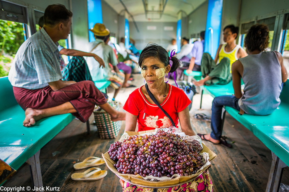 15 JUNE 2013 - YANGON, MYANMAR: A grape vendor on the Yangon Circular Train. The Yangon Circular Railway is the local commuter rail network that serves the Yangon metropolitan area. Operated by Myanmar Railways, the 45.9-kilometre (28.5mi) 39-station loop system connects satellite towns and suburban areas to the city. The railway has about 200 coaches, runs 20 times and sells 100,000 to 150,000 tickets daily. The loop, which takes about three hours to complete, is a popular for tourists to see a cross section of life in Yangon. The trains from 3:45 am to 10:15 pm daily. The cost of a ticket for a distance of 15 miles is ten kyats (~nine US cents), and that for over 15 miles is twenty kyats (~18 US cents). Foreigners pay 1 USD (Kyat not accepted), regardless of the length of the journey.     PHOTO BY JACK KURTZ