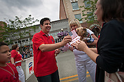 Republican Congressional Candidate for Idaho's First District Raul Labrador hands out American flags to parade-goers on Sherman Avenue during Sunday's Fourth of July Parade in Coeur d'Alene.