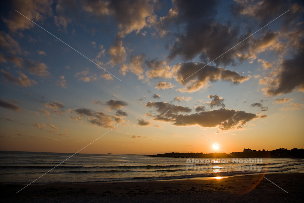 USA, Newport, RI - Sunset at Reject's Beach under puffy clouds. Rejects is the publicly accessible portion of the private Bailey's Beach.