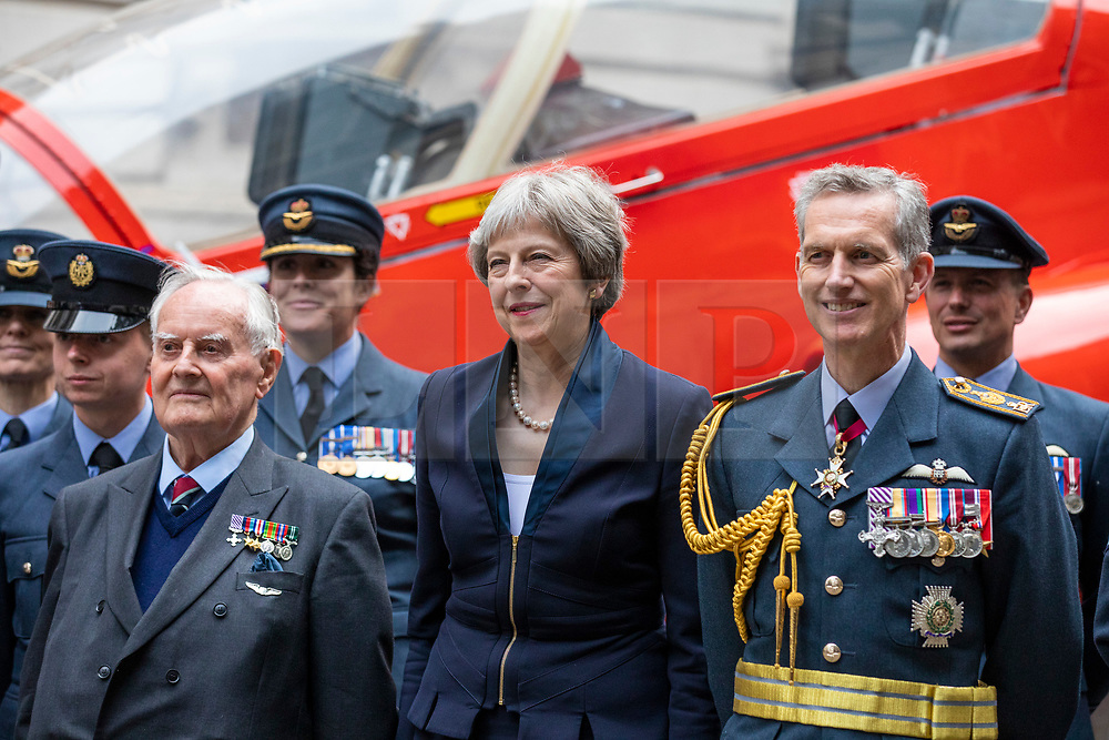© Licensed to London News Pictures. 23/05/2018. London, UK. Prime Minister Theresa May (centre), 92-year-old WW2 pilot Colin Bell (centre-left) and Air Chief Marshal Sir Stephen Hillier(centre-right) pose for a photograph with members of the RAF in front of a Red Arrow jet as part of the RAF100 Centenary celebrations. Photo credit: Rob Pinney/LNP