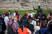 Tourists listen to a tour guide speaking at the Julius Caesar statue at at Tower Hill, London. This is one of the most popular tourist destintions in London. One of the earliest stories associated with the Tower was that it was built by Julius Caesar. The earliest recorded attribution of the Tower to the Roman ruler dates to the mid-14thcentury in a poem by Sir Thomas Gray. The origin of the myth is uncertain, although it may be related to the fact that the Tower was built in the corner of London's Roman walls.