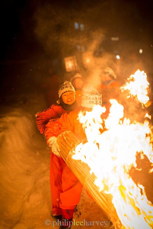 Children holding burning straw at night, Nozawaonsen, Japan