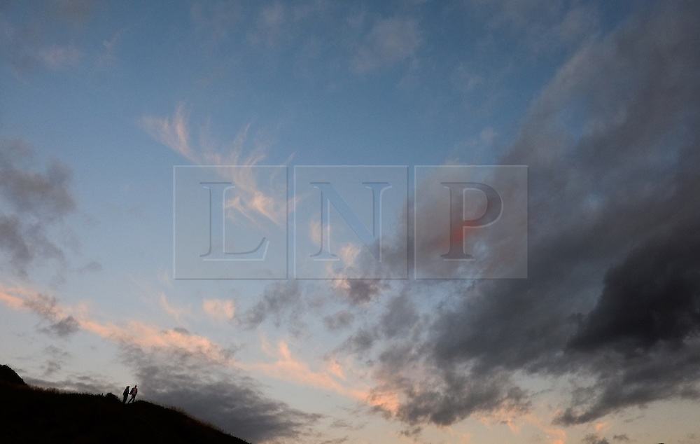 © Licensed to London News Pictures.06/08/15<br /> Saltburn, UK. <br /> <br /> A couple walk down a hill known locally as Cat Nab at sunset at Saltburn by the Sea in Cleveland. <br /> <br /> Photo credit : Ian Forsyth/LNP