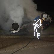 Autobrand Gemeenlandslaan Huizen, auto op de kop, brandweer blussen, vernieling, rook