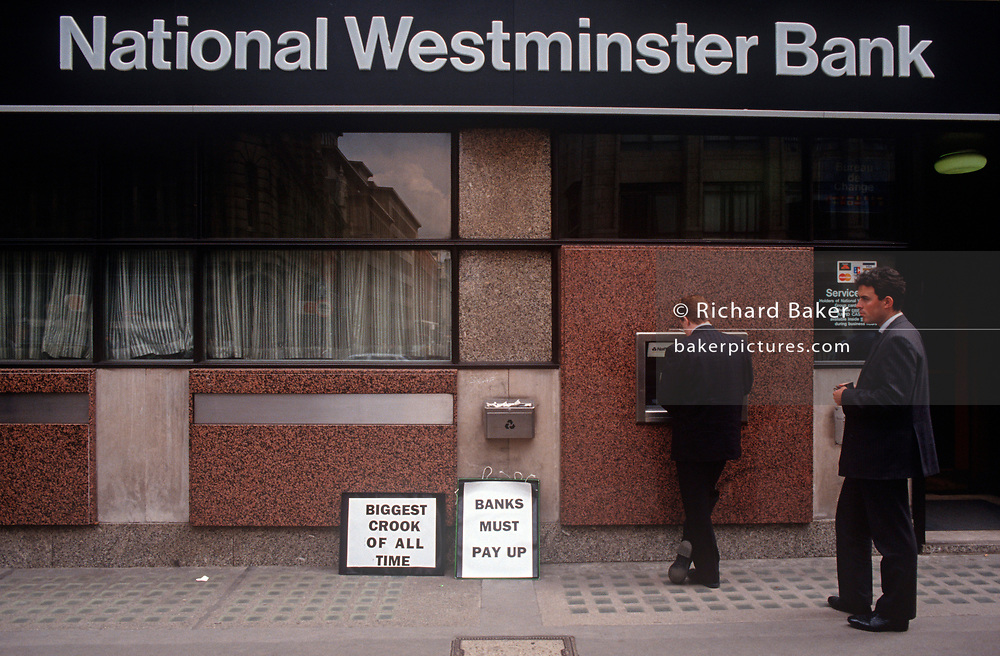 Two businessmen use the cash dispenser outside a branch of National Westminster Bank (Natwest) in the City of London (aka The Square Mile), the capital's financial centre, on 16th June 1994, in London, England. (Photo by Richard Baker / In Pictures via Getty Images)