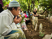 17 JULY 2015 - BANGKOK, THAILAND:     A man prays in the cemetery of Ton Son Mosque after Eid services at the mosque in Bangkok. Eid al-Fitr is also called Feast of Breaking the Fast, the Sugar Feast, Bayram (Bajram), the Sweet Festival or Hari Raya Puasa and the Lesser Eid. It is an important Muslim religious holiday that marks the end of Ramadan, the Islamic holy month of fasting. Muslims are not allowed to fast on Eid. The holiday celebrates the conclusion of the 29 or 30 days of dawn-to-sunset fasting Muslims do during the month of Ramadan. Islam is the second largest religion in Thailand. Government sources say about 5% of Thais are Muslim, many in the Muslim community say the number is closer to 10%.          PHOTO BY JACK KURTZ