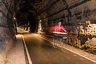 Cyclist riding in the Combe Down tunnel. At 1672m long this is claimed (by Sustrans) to be the longest tunnel in Europe on a cycle route.