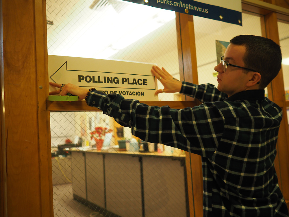 An Arlington, VA election official hangs signs in preparation for the opening of polls on Presidential Primary Day.