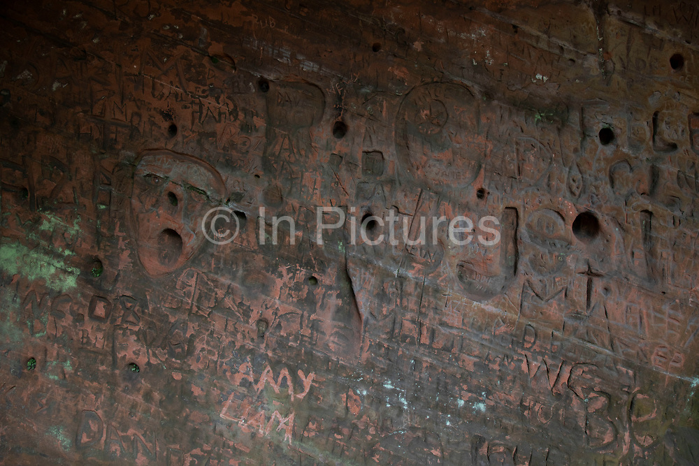 Carvings into a sandstone cave. Kinver Edge is home to the last troglodyte dwellings occupied in England, with a set of complete cave-houses excavated into the local sandstone at Kinver, United Kingdom. One of the rocks, 'Holy Austin', was a hermitage until the Reformation. The Holy Austin rock houses were inhabited until the 1960s. They are owned by the National Trust and are open for tour. One house has been restored to a Victorian appearance, and the Martindale Caves show what life was like in the 1930s. Kinver Edge is a high heath and woodland escarpment just west of Kinver, and is on the border between Worcestershire and Staffordshire.