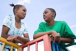 Bother and sister; on a climbing frame; talking to each other,