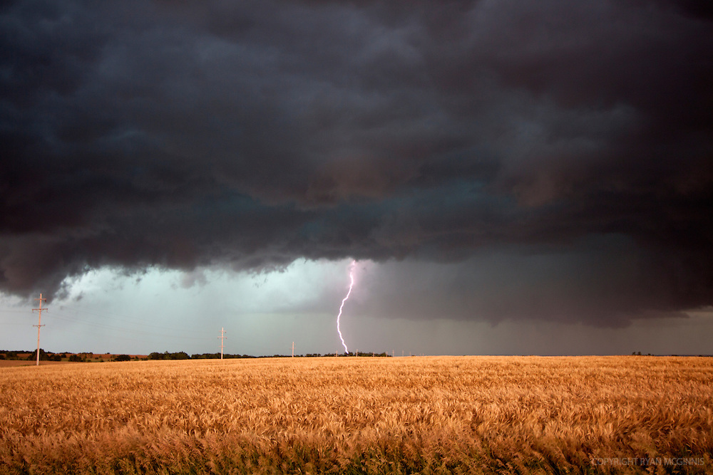 A solo lightning bolt strikes the prairie beneath a supercell thunderstorm in Kansas.