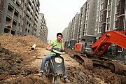 A man rides his bike through the construction site of a new housing development  in Yangzhou, Jiangsu Province, China on 19 July 2012. While the Chinese government has tried various ways to cool down the property market, real estate prices have still seen a steady increase in recent years, proving hard for the country to move away from an investment driven economy.