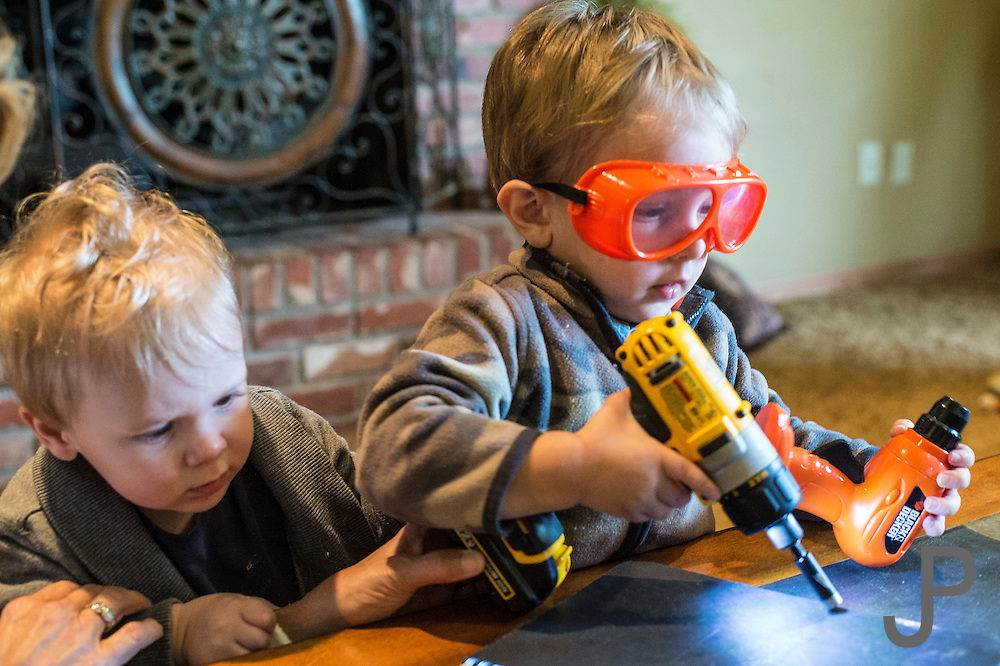 Jamison and Charlie Pratt playing with a cordless drill