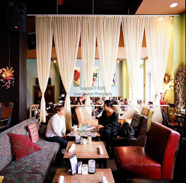 Busboys and Poets is a restaurant, bookstore, fair trade market and gathering place where people can discuss issues of social justice and peace. Busboys and Poets creates an environment where shared conversations over food and drink allow the progressive, artistic and literary communities to dialogue, educate and interact. Pictured here is the middle area of the facility, where couches and informal seating areas afford customers a more casual environment.