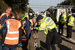 Ockham, UK. 21st September, 2021. Surrey Police officers arrest Insulate Britain climate activist Reverend Sue Parfitt who had previously blocked the clockwise carriageway of the M25 between Junctions 9 and 10 as part of a campaign intended to push the UK government to make significant legislative change to start lowering emissions. Activists briefly halted traffic on both carriageways of the motorway before being removed and arrested by Surrey Police.