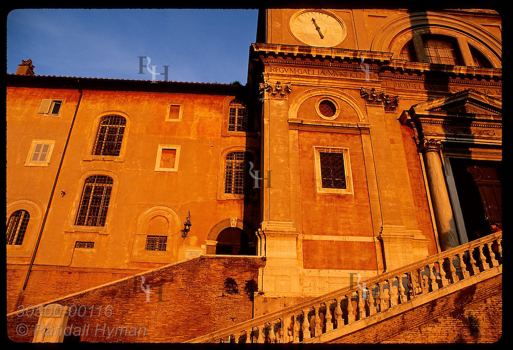 January sunset bathes the Trinita dei Monti church in gold as woman stands on steps; Rome. Italy