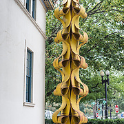 A yellow metal sculpture outside the main entrance of the Art Museum of the Americas, housed in a 1912 Spanish colonial building that is part of the Organization of American States complex in Washington DC's Foggy Bottom district.