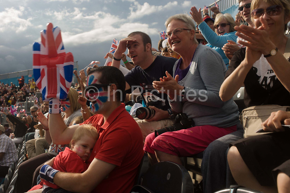 As a little boy drifts off to sleep, a father with a painted face holds a giant union jack hand as British fans cheer on their hero David Florence during the canoe slalom heats at the Lee Valley White Water Centre, north east London, on day 3 of the London 2012 Olympic Games.