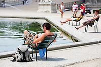 tourist resting and reading in a park of paris during summer heat wave
