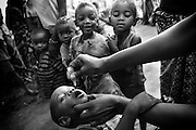 A child receives two drops of polio vaccine during the second round of vaccination in Djambala Village, Republic of Congo on Wednesday December 8, 2010.