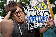 A young Japanese man gives the middle finger while holding an anti fascist sign at a protest against the revision of article 9 of the Japanese Constitution outside the Prime-Minister's house in Kasumigasaki, Tokyo, Japan. Monday June 30th 2014. Over 10,000 people showed their support for Japan's unique peace constitution and called on the government to halt its reinterpretation of Article 9 allowing collective Self Defence, which means Japanese Self Defence Forces will be allowed to take part in wars with Japan's allies. The reinterpretations is  expected to become law on July 1st