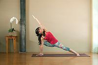 Woman in her 40's practicing the yoga pose Side Angle; Utthita Parsvakonasana.