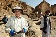 Professor Zemaryali Tarzi, (left) a notable An Afghan-born archaeologist from France and teacher in Strasbourg University, is portrayed on his excavation field while searching for a legendary 300m Sleeping Buddha statue between the original standing Buddhas of Bamiyan, Afghanistan, as documented in the old account of a renowned Chinese scholar, Xuanzang, visiting the area in the 7th century. The Buddhas of Bamiyan were two 6th century monumental statues of standing Buddhas carved into the side of a cliff in the Bamiyan valley in the Hazarajat region of central Afghanistan, situated 230 km northwest of Kabul at an altitude of 2500 meters. The statues represented the classic blended style of Gandhara art. The main bodies were hewn directly from the sandstone cliffs, but details were modelled in mud mixed with straw, coated with stucco. Amid widespread international condemnation, the smaller statues (55 and 39 meters respectively) were intentionally dynamited and destroyed in 2001 by the Taliban because they believed them to be un-Islamic idols. Once a stopping point along the Silk Road between China and the Middle East, researchers think Bamiyan was the site of monasteries housing as many as 5,000 monks during its peak as a Buddhist centre in the 6th and 7th centuries. It is now a UNESCO Heritage Site since 2003. Archaeologists from various countries across the world have been engaged in preservation, general maintenance around the site and renovation. Professor Tarzi worked on projects to restore the other Bamiyan Buddhas in the late 1970s and has spent most of his career researching the existence of the missing giant Buddha in the valley.