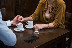 Midsection of couple holding hands while coffee and mobile phone on table