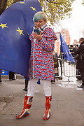 A young woman wearing a Union Jack raincoat and wellington boots looks at her mobile phone outside the Houses of Parliament the day after Theresa Mays crushing defeat over her Brexit deal on the 16th January 2019 in London in the United Kingdom.