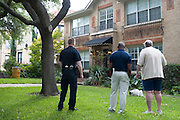 A police officer and Dallas official speak with a neighbor outside the apartment where a second Ebola patient has been reported in Dallas, Texas on October 12, 2014. (Cooper Neill for The New York Times)
