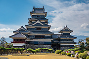"""East face of Matsumoto Castle, built 1592-1614. Matsumoto, Nagano Prefecture, Japan. Matsumoto Castle is a """"hirajiro"""" - a castle built on plains rather than on a hill or mountain. Matsumotojo's main castle keep and its smaller, second donjon were built from 1592 to 1614, well-fortified as peace was not yet fully achieved at the time. In 1635, when military threats had ceased, a third, barely defended turret and another for moon viewing were added to the castle. Interesting features of the castle include steep wooden stairs, openings to drop stones onto invaders, openings for archers, as well as an observation deck at the top, sixth floor of the main keep with views over the Matsumoto city."""