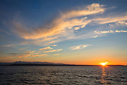 Several cirrus clouds color the sky over Puget Sound and the Olympic Mountains in this view from the Edmonds, Washington, waterfront.