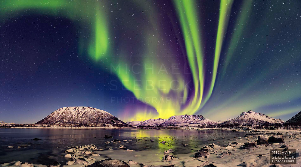 A dazzling aurora illuminates the night sky over a fjord in Nordland, Norway.<br /> <br /> Limited Edition of 125