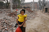 A mingong and his son return to the camp in Sanlitun where they live, Beijing, China.