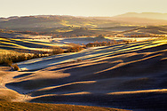 Brushstrokes of light at dawn on a winter morning, illuminate the Tuscan hills of the Orcia Valley in the province of Siena in Tuscany, Italy