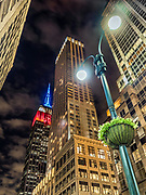 The Empire State Building lit up in blue and red colors in Manhattan, New York City.