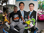 22 JUNE 2011 - BANGKOK, THAILAND: A man sits on his motorcycle in front of a campaign poster for Thai incumbent Prime Minister Abhisiti Vejjajiva in Bangkok Wednesday. Yingluck Shinawatra, leader of the Pheua Thai party is running against  incumbent Prime Minister Abhisit Vejjajiva, head of the Democrat party. Yingluck is the youngest sister of exiled former Prime Minister Thaksin Shinawatra, deposed by a military coup in 2006. Yingluck is currently leading in opinion polls, running well ahead of the Democrat party, which in one form or another has ruled Thailand for most of the last 60 years.   Photo by Jack Kurtz