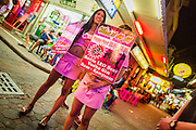 """26 SEPTEMBER 2014 - PATTAYA, CHONBURI, THAILAND: Touts try to lure tourists into bars on Walking Street in Pataya. Pataya, a beach resort about two hours from Bangkok, has wrestled with a reputation of having a high crime rate and being a haven for sex tourism. After the coup in May, the military government cracked down on other Thai beach resorts, notably Phuket and Hua Hin, putting military officers in charge of law enforcement and cleaning up unlicensed businesses that encroached on beaches. Pattaya city officials have launched their own crackdown and clean up in order to prevent a military crackdown. City officials have vowed to remake Pattaya as a """"family friendly"""" destination. City police and tourist police now patrol """"Walking Street,"""" Pattaya's notorious red light district, and officials are cracking down on unlicensed businesses on the beach.     PHOTO BY JACK KURTZ"""